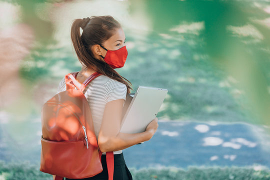 Back to school university student Asian woman wearing face mask on campus walking with red backpack, books and laptop. Coronavirus reality.