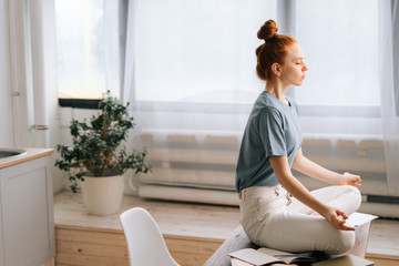 Side view of peaceful redhead young woman is meditating while sitting on desk at home office. Carefree female sitting in lotus pose with closed eyes on background of large window.