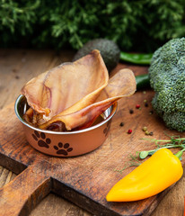 Dried pig ears in the dog vessel among the greenery on the wooden board. Chewing treats for domestic dogs. Natural dental treats for promotion and pampering.