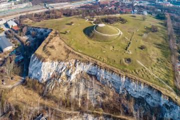 Fototapeta Krakus Mound - Kopiec Krakusa commemorating a legendary founder of Krakow. The origin of the mound, probably early medieval kurgan, is not known. Old quarry in front. City panorama in the background obraz