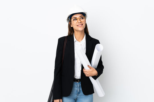 Young architect caucasian woman with helmet and holding blueprints over isolated background laughing and looking up