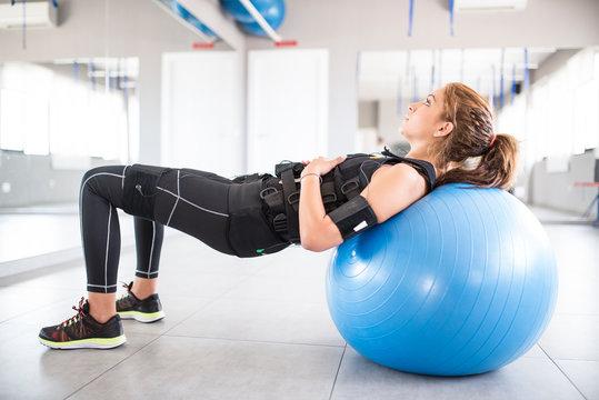 Woman training with electro stimulator