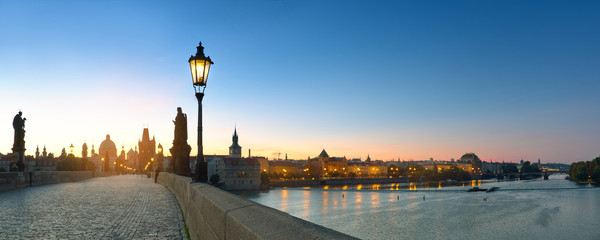 Fotomurales - Charles Bridge at dawn. Panoramic image, silhouette of Bridge Tower and churches, street lights in Prague, Czech Republic.