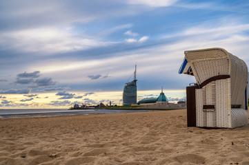 Blick entlang der Küste von Bremerhaven mit Sandstrand im Vordergrund und Bauwerken und Hafen im Hintergrund Fotobehang