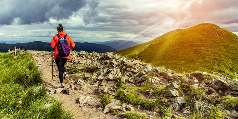Girl hiking in mountains at sunset. Hiking trail in Bieszczady Poland. Lonley hiker in the mountains. Woman conquer mountains.