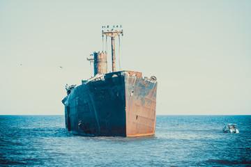 Acrylic Prints Shipwreck A shipwreck on a sandbank in the sea. Rusty wreck abandoned at sea.