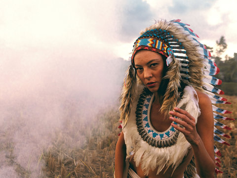 Young woman dressed as a North American Indian in a field. Pocahontas.