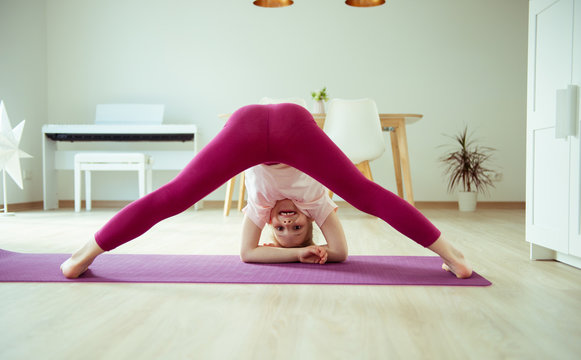 Pretty child girl having fun making yoga exercises at home