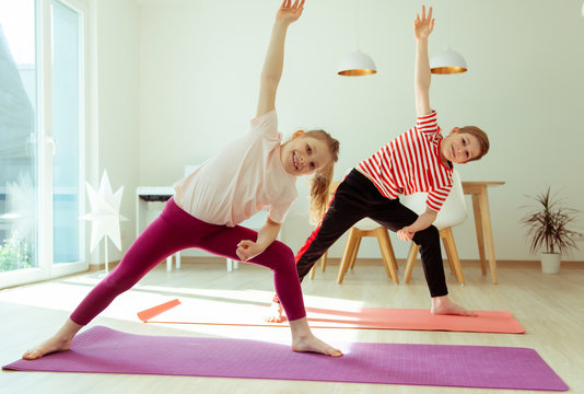Happy siblings children making yoga at home