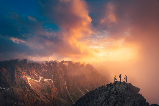 Team success concept photo, friends standing together on the top of the hill, over beautiful mountains landscape in gold sunset light, orange edit space..