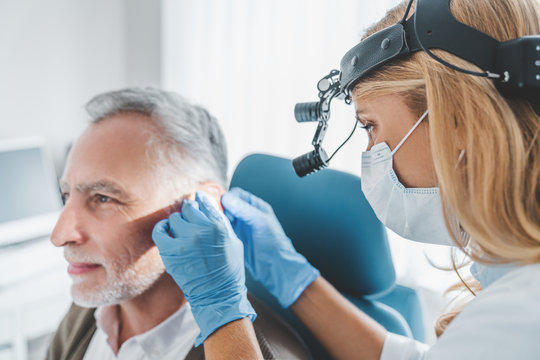 Mature patient with hearing problem visiting doctor otolaryngologist