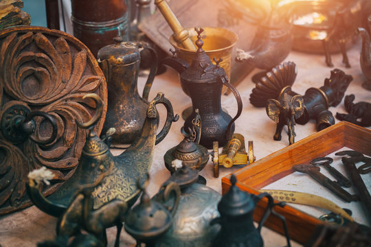 Vintage metal trinkets of elephant, cannon, deer next to metal oil lamp, rusty keys and bronze mortar,  jugs and on the countertop at sunday flea market. Vintage furniture in antique bazaar.