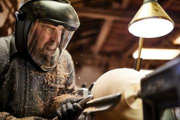 Craftsman doing woodwork on turning machine