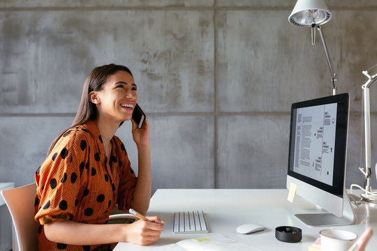 Female employee speaking on phone and laughing