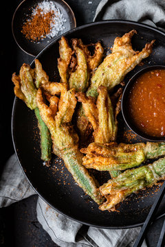Zucchini flowers in tempura with spicy sauce and spices