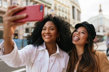 African american and asian women taking a selfie