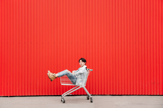 Young Asian Man Sitting in Cart against Red Background