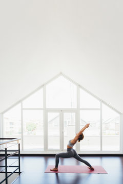 Back view of beautiful young woman doing yoga postures in luxury apartment