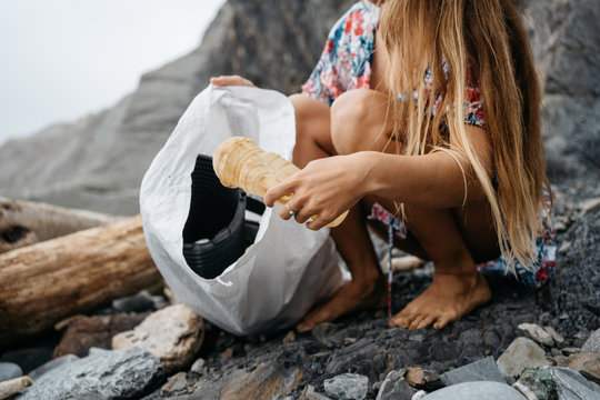 Anonymous volunteer cleaning beach from plastic