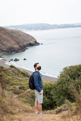 Man social distancing and wearing a face mask on a coastal hiking trail