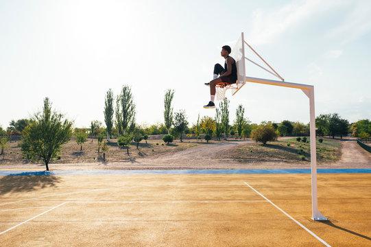 Black player sitting on basketball hoop holding leg