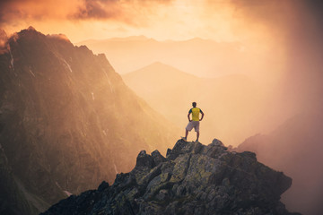 Man on the top of the hill watching wonderful scenery in mountains during summer colorful sunset in High Tatras in Slovakia. Travel, adventure or expedition concept..