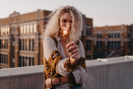 A young blonde woman in her twenties on a rooftop at sunset