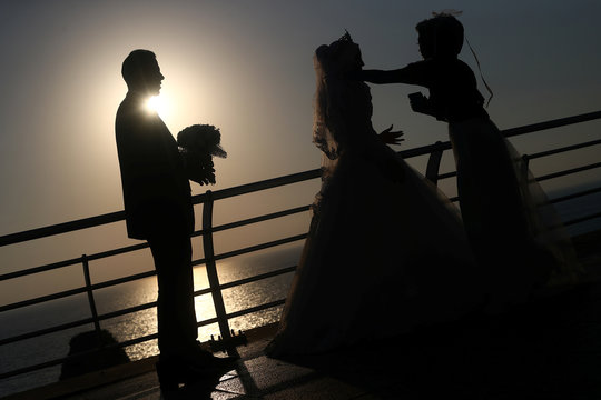 A couple prepares to pose for their wedding photos, near the Raouche Rocks in Beirut