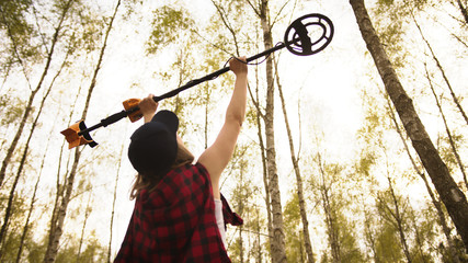 Treasure hunter, young woman holding metal detector in the air in the forest. Low angle. High quality photo