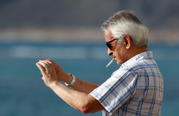 A man smokes a cigarette while taking a picture with his cell phone during the spread of the coronavirus disease (COVID-19) pandemic, in Las Palmas