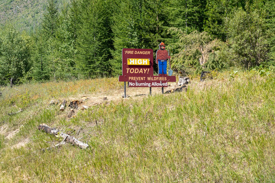 Polebridge, Montana - July 28, 2020: Sign along the road in the Flathead National Forest has Smokey the Bear warning of Fire Danger High today, for wildfires