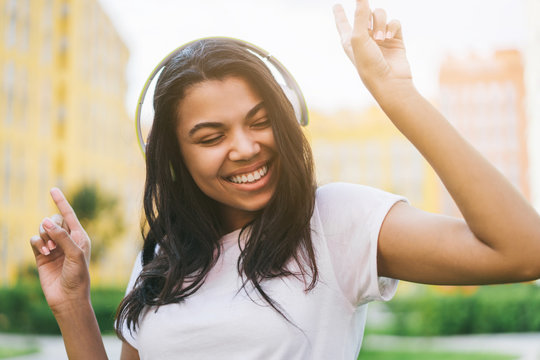 Pretty dark skinned girl with charming smile having fun outdoors listening to music and dancing