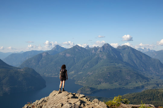 Adventurous Girl Hiking on top of Tin Hat Mountain, part of the popular Sunshine Coast Hiking Trail in Powell River, British Columbia, Canada. Concept: Explore, Adventure, Travel