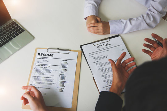 Office job interviews with HR personnel holding resume and background checks on applicants with prepared skills.