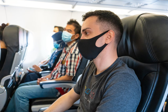 Airplane passengers are wearing medical masks on their faces. Air travel during the coronavirus pandemic. Airlines requirements.