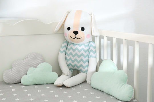 Cute toy dog and cloud shaped pillows in crib, closeup. Baby room interior elements