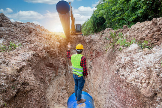 Engineer wear safety uniform examining excavation Drainage Pipe and Large plumbing water system underground at construction site.