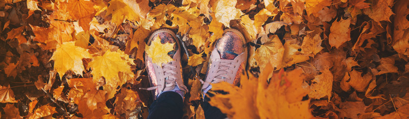 Children in the park with autumn leaves on shoes. Selective focus.