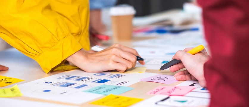 Close up hand ux developer and ui designer brainstorming about mobile app interface wireframe design on table at modern office.Creative digital development agency