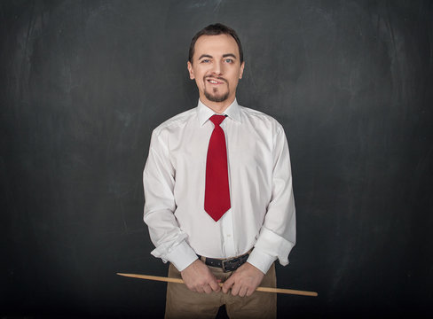 Smirking teacher or business man with pointer on blackboard