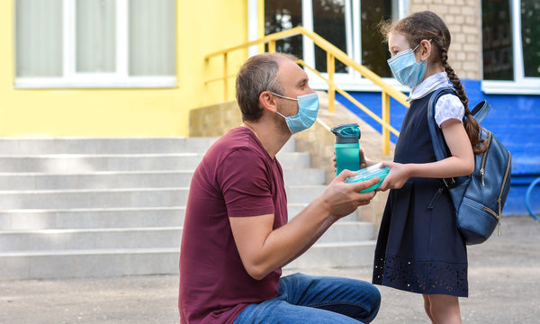 A schoolgirl wearing a medical mask goes back to school after the coronavirus outbreak. Surgical masks for coronavirus prevention. Masked parents accompany their children to school