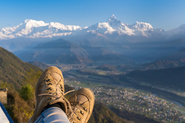 Legs of traveler in hiking shoes sitting on high mountain cliff enjoying scenery mountain. Travel, freedom, trekking and hiking concept. Stock photo