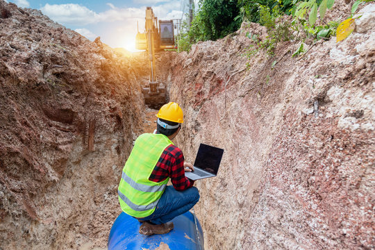 Engineer wear safety uniform use laptop examining excavation Drainage Pipe and Large plumbing water system underground at construction site.
