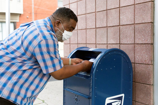 An individual deposits letters into a U.S. Postal Service (USPS) collection mailbox in Philadelphia