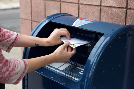 An individual mails letters through the U.S. Postal Service (USPS) in Philadelphia