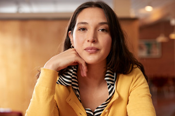 Portrait of young ethnic woman wearing yellow sweater with black and white striped blouse sitting at bar in kitchen of downtown loft
