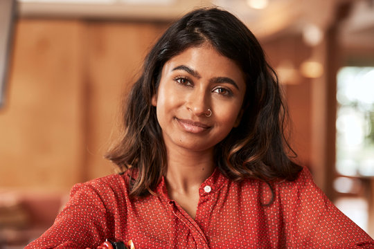 Portrait of young ethnic woman wearing orange blouse sitting at bar in kitchen of downtown loft