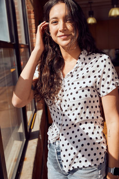 Portrait of a young ethnic woman wearing polka dot blouse and cut off jean shorts standing by bank of windows in a downtown loft