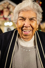 Older Hispanic woman smiling outside house decorated with string lights