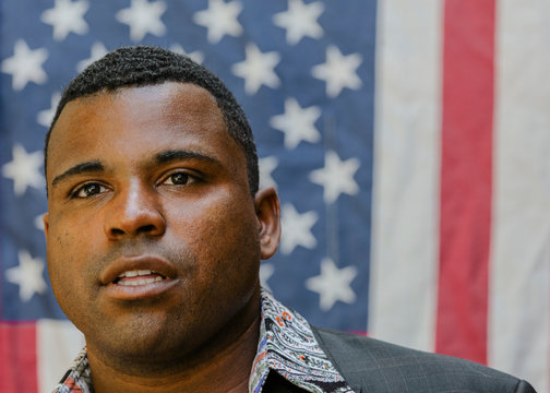 Close up of Black man in front of American flag